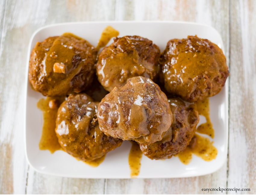Crock Pot Salisbury Steak patties cooked and stacked on a serving plate and drizzled with gravy.