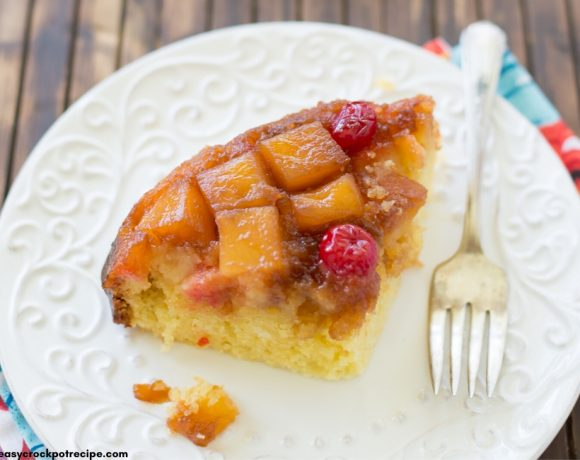 A slice of Crock Pot Pineapple Upside Down Cake on a white plate with a colorful napkin behind it.