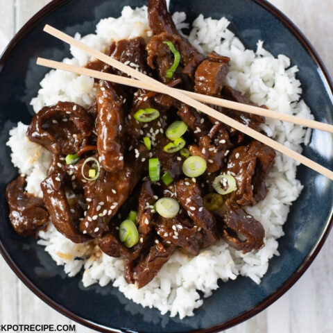 a dark blue bowl filled with tender Crock Pot Mongolian Beef served over a bed of cooked white rice with sliced green onions as the garnish.