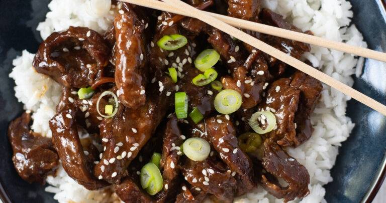 a serving of mongolian beef over white rice is a bowl