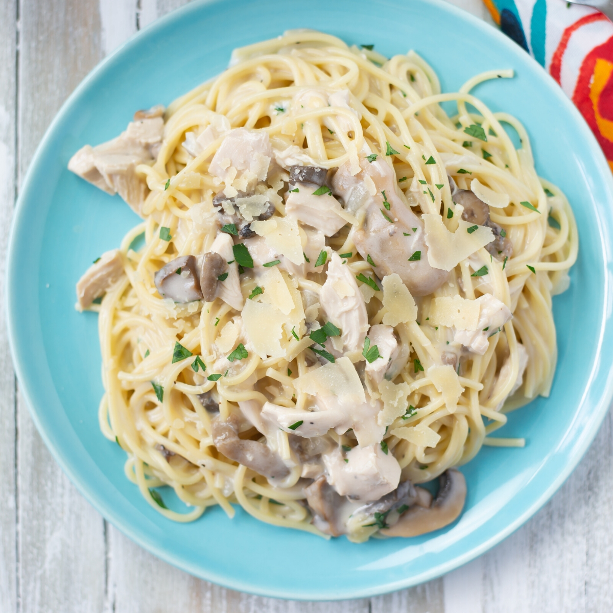 A blue plate with a serving of Crock Pot Chicken Tetrazzini